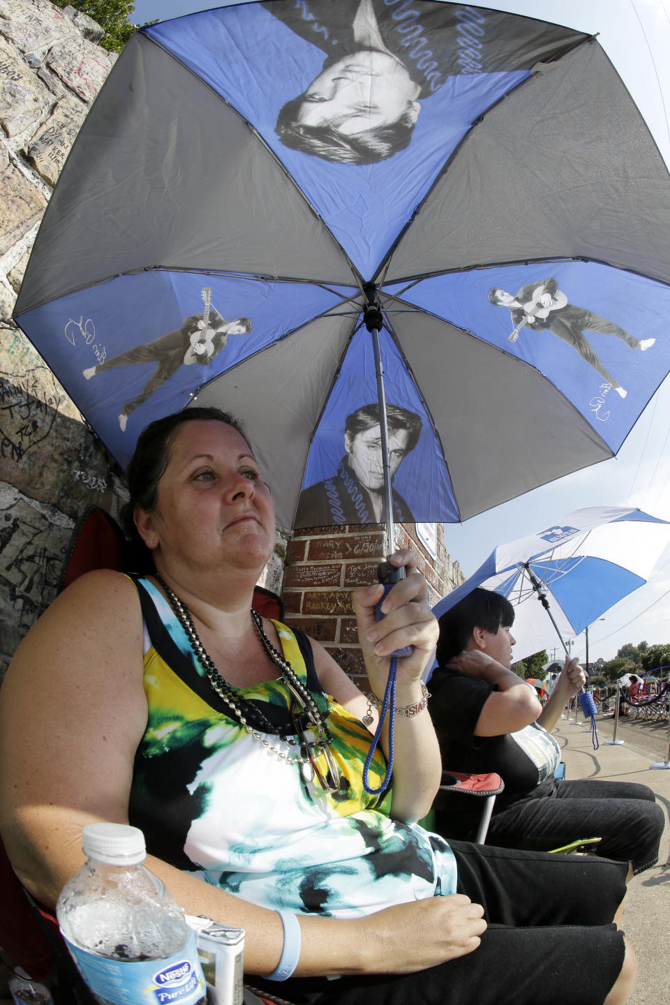 Elvis Presley fan Mary Ann Seiber, from Knoxville, Tenn., waits in line outside Graceland, Presley's Memphis, Tenn. home, on Wednesday, Aug. 15, 2012. Fans are lined up to take part in the annual candlelight vigil marking the 35th anniversary of Presley's death. (AP Photo/Mark Humphrey)
