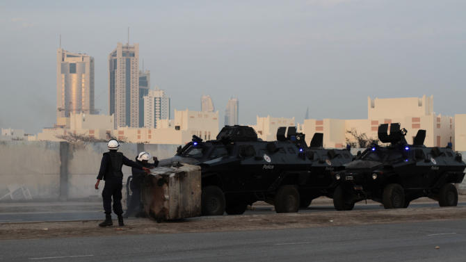 Riot police clear the way for the armored vehicles to pass along a highway on the outskirts of the capital of Manama during clashes with Bahraini anti-government protesters in Sanabis, Bahrain, Tuesday, Feb. 12, 2013. Clashes erupted at the end of an anti-government march, when hundreds of youths attempted to reach the heavily guarded site of the 2011 pro-democracy uprising. (AP Photo/Hasan Jamali)