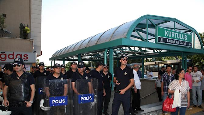 "Riot police stand at the entrance in anticipation of young Turkish couples expected to kiss in protest against subway official's harassment of a couple for kissing in public last week, at a subway stop in Ankara, Turkey, Saturday, May 25, 2013.  Last week, Ankara subway officials made a reproaching announcement asking passengers ""to act in accordance with moral rules,"" after spotting the couple kissing through security cameras.(AP Photo/Burhan Ozbilici)"