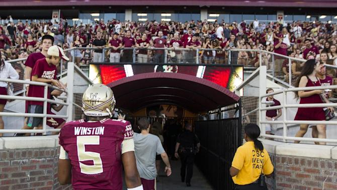 Suspended Heisman quarterback Jameis Winston, who dressed in full pads for pre game warm ups, returns to the locker room to change before FSU's NCAA college football game against Clemson in Tallahassee, Fla., Saturday, Sept. 20, 2014. Winston rejoined his teammates  in regular clothes