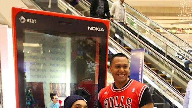 IMAGE DISTRIBUTED FOR NOKIA - Chicago Bulls center Joakim Noah, left, greets his fans with his new Nokia Lumia 920 at the Nokia Experience Center, during the Joakim Noah Nokia Mall Tour, on Thursday, Dec. 13, 2012 in Schaumburg, Ill. (Photo by Barry Brecheisen/Invision for Nokia/AP Images)