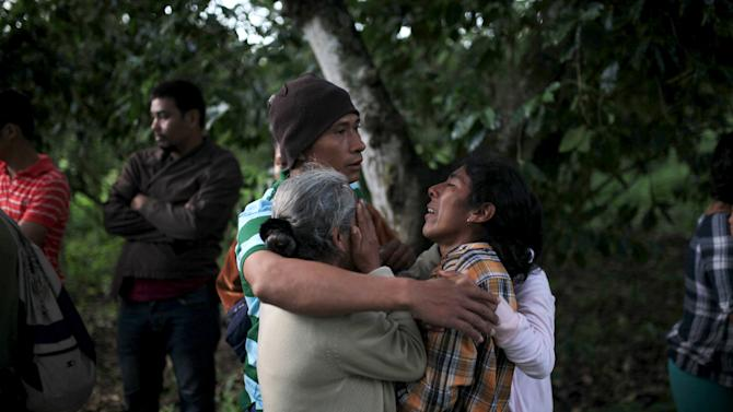 Relatives react as police investigators work at a crime scene where four men were executed in the town of Nuevo Cuscatlan