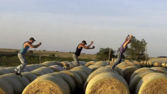 """This frame grab from video shows Assaria, Kan., brothers, from left: Nathan; Kendal and Greg Peterson in their video parody on LMAFO's """"Sexy and I Know It.""""  The parody, that has gone viral on YouTube and Facebook, shows the three brothers rapping their farming mission on the family's Saline County farm. (AP Photo/Courtesy Greg Peterson)"""