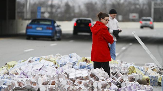 A member from the Health Department checks the condition of ice cream that spilled on Interstate 69, Friday, Dec. 23, 2011, in Fort Wayne, Ind. Police said 40,000 pounds of ice cream spilled from a semitrailer closing two lanes of I-69 at the start of the holiday weekend. (AP Photo/The Journal-Gazette, Michelle Davies) MANDATORY CREDIT.