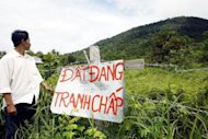 This file photo shows a Vietnamese villager standing next to a sign that reads 'Land in dispute.' Hundreds of villagers stormed a local government office in Vietnam, smashing furniture and seriously injuring two officials in connection with a land dispute, state media said on Thursday