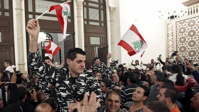 Lebanese soldiers and policemen who were captured by the al Qaeda-linked Nusra Front in Arsal, celebrate carrying Lebanese flags upon their arrival in Beirut