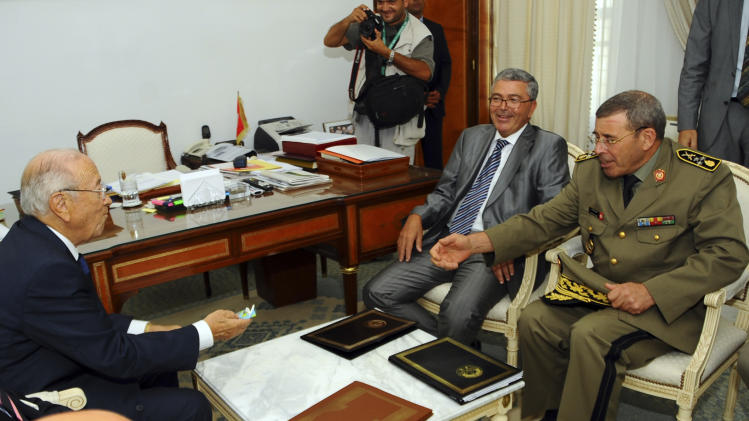 Tunisia's prime minister Beji Caid-Essebsi, left, talks with Chief of Staff Gen. Rachid Ammar, right,  and Defense Minister Abdelkarim Zbidi, in Tunis, Tuesday, Sept.6, 2011. Caid-Essebsi says authorities are stepping up enforcement of a state of emergency after pockets of violence erupted in recent days, new instability after the country's revolution.(AP Photo/Hassene Dridi)
