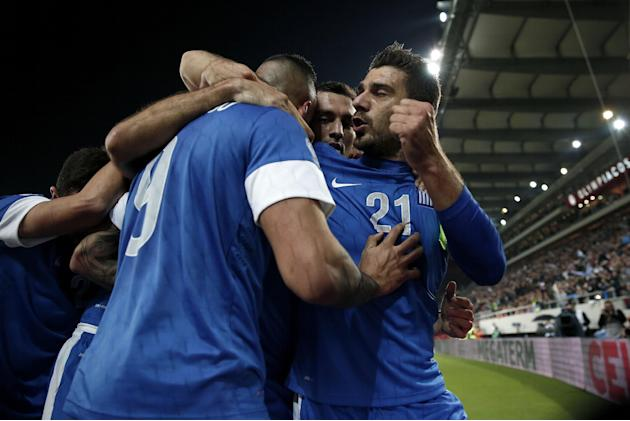 Greece's Kostas Katsouranis, right, celebrates his goal with teammates during their World Cup qualifying playoff first leg soccer match against Romania at the Karaiskaki stadium in the port of Piraeus