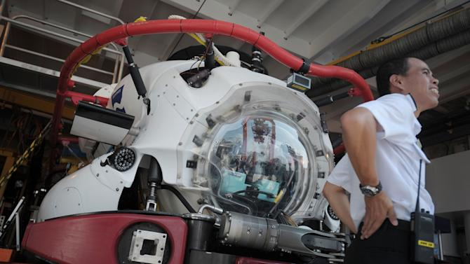A Singapore naval officer stretches by a Submarine Rescue Vehicle on board the MV Swift Rescue, a private submarine rescue vessel contracted to the Republic of Singapore Navy on Thursday May 19, 2011 in Singapore during the International Maritime Defense Show.(AP Photo/Joseph Nair)
