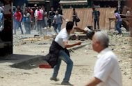 Unidentified Egyptians (top) throw stones at anti-military protesters during clashes in the Abbassiya district of Cairo. Thugs attacked an anti-military protest near the defence ministry in Cairo and 20 people were killed, officials said, in the politically tense run-up to the first post-uprising presidential election