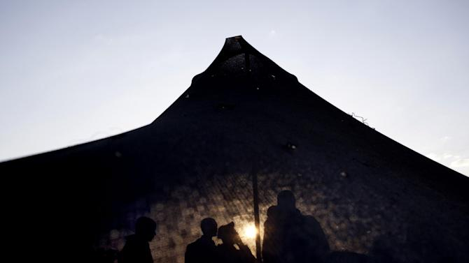 Israeli soldiers of the Golani brigade gather in a tent, as the sun rises, before a military exercise in the Israeli controlled Golan Heights, near the border with Syria, Tuesday, May 7, 2013. (AP Photo/Ariel Schalit)