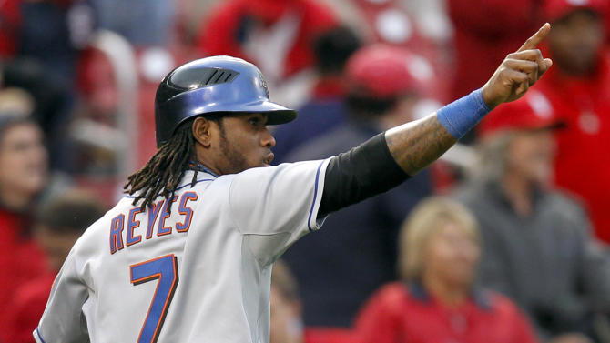 New York Mets' Jose Reyes points to teammate Willie Harris after Reyes scored on a two-run single by Harris during the ninth inning of a baseball game Thursday, Sept. 22, 2011, in St. Louis. The Mets won 8-6. (AP Photo/Jeff Roberson)