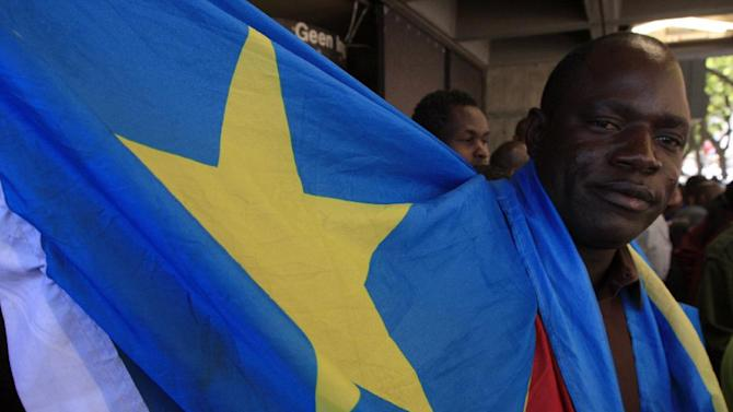 A supporter wrapped in a Democratic Repupublic of Congo flag stands outside the court in Pretoria, South Africa, on Thursday, Feb. 7, 2013. Nineteen alleged members of a Congolese rebel group — including one U.S. citizen — sought help in their effort to overthrow Congolese President Joseph Kabila, offering mining rights in their resource-rich country in exchange for weapons and training, a prosecutor said Thursday. (AP Photo/Jon Gambrell)