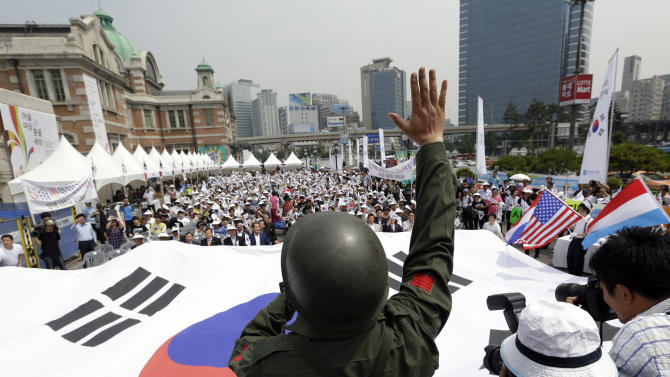 A member of Korea Freedom Federation wearing the South Korean soldier uniform, shout slogans as others carry a huge national flag during a ceremony to mark the 63rd anniversary of the outbreak of the Korean War in Seoul, South Korea, Tuesday, June 25, 2013. The three-year Korean War broke out on June 25, 1950, when Soviet tank-led North Koreans invaded South Korea. (AP Photo/Lee Jin-man)