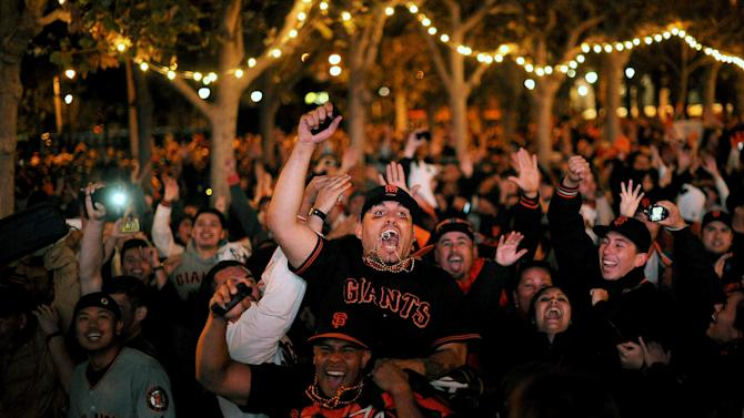 San Francisco Giants fan Gevo Lopez celebrates with others outside San Francisco's City Hall while watching a broadcast of the Giants facing the Detroit Tigers in Game 4 of baseball's World Series on Sunday, Oct. 28, 2012. The Giants won the game to sweep the series. (AP Photo/Noah Berger)
