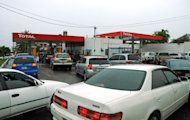 Drivers wait to fill their cars with fuel as rain brought by the outer bands of Tropical Storm Sandy fall in Kingston, Jamaica, Tuesday, Oct. 23, 2012. The U.S. National Hurricane Center in Miami said Sandy was expected to become a hurricane as it nears Jamaica on Wednesday. (AP Photo/Collin Reid)