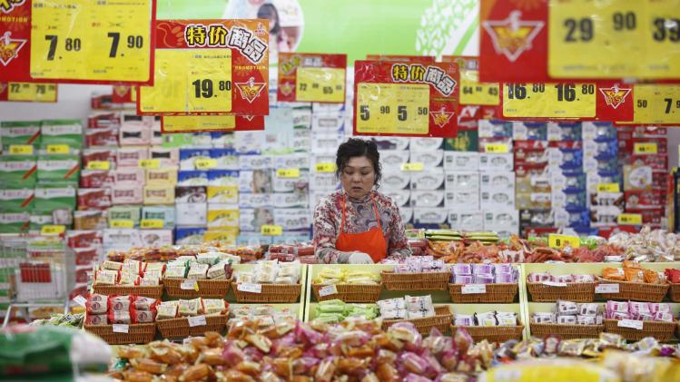 An employee arranges stock at a supermarket in Huaibei