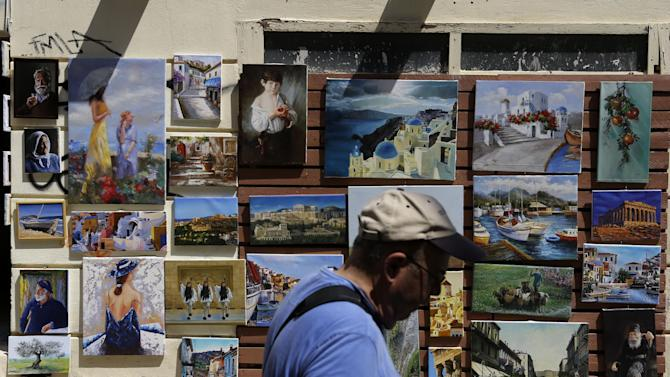 A man passes a shops with  paintings of scene of  Greece in the Plaka tourist district of Athens, Tuesday, July 28, 2015. Emissaries from Greece's international creditors are holding preparatory talks with Greek officials as the aim is to thrash out the terms of the deal before Aug. 20, when Greece must make a debt payment that it cannot afford without new loans. (AP Photo/Thanassis Stavrakis)