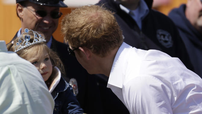 Britain's Prince Harry, right, talks to a young girl at Casino Pier during a tour of the area hit by Superstorm Sandy, Tuesday, May 14, 2013, in Seaside Heights, N.J. The prince toured the community's rebuilt boardwalk, which is about two-thirds complete. New Jersey sustained about $37 billion worth of damage from the storm. (AP Photo/Julio Cortez)