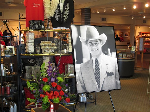 A large portrait of Larry Hagman can be seen by a bouquet of flowers at the entrance of the gift shop at Southfork Ranch on Saturday, Nov. 24, 2012, in Parker, Texas. Officials at the ranch, the setting for the TV series &quot;Dallas&quot; where Hagman played the infamous J.R. Ewing, placed the photo there in memory of Hagman, who died Friday, Nov. 23, 2012 in Dallas. He was 81. (AP Photo/Angela K. Brown)