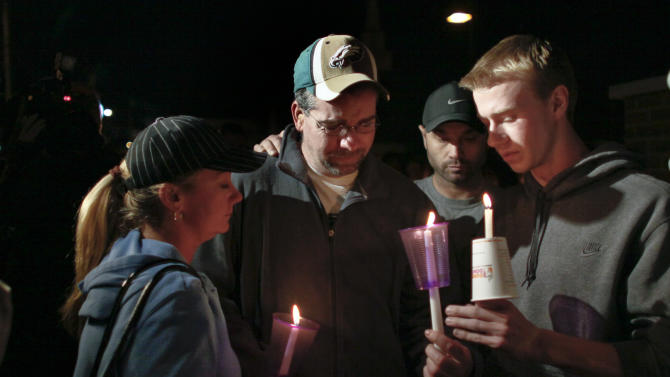 Anthony Pasquale, second from left, father of Autumn Pasquale, is comforted during a candlelight vigil for the missing girl, Monday Oct. 22, 2012, in Clayton, N.J. About 200 law enforcement officials and hundreds more volunteers searched Monday for Autumn, a southern New Jersey girl who disappeared over the weekend, raising anxiety in a rural town and pulling residents together. (AP Photo/Joseph Kaczmarek)