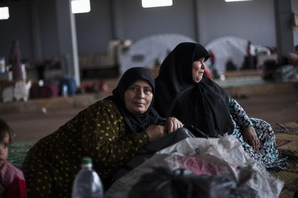 Two Syrian women take a rest within a refugee camp in the border with Turkey, near Azaz village, Syria, Sunday, Sept. 30, 2012. (AP Photo/ Manu Brabo)