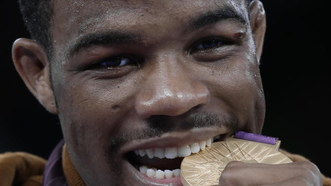 United States' Jordan Ernest Burroughs bites his gold medal after men's 74-kg freestyle wrestling competition at the 2012 Summer Olympics, Friday, Aug. 10, 2012, in London. (AP Photo/Paul Sancya)