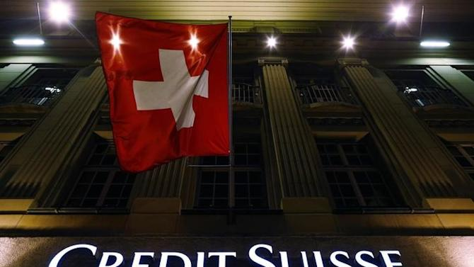 Logo of Swiss bank Credit Suisse is seen below the Swiss national flag at a building in the Federal Square in Bern
