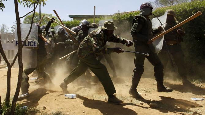 Riot policemen run to take cover after dispersing residents during protests to oust Narok county Governor Samuel Tunai in Narok, Kenya