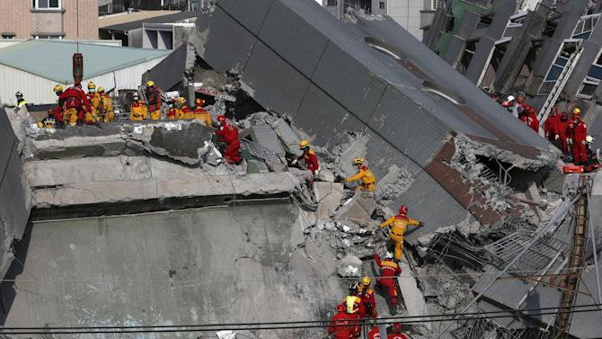 Rescue personnel search the rubble of a 17-storey apartment building that collapsed after an earthquake hit Tainan