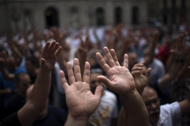 Public transport workers raise their hands as they march protesting during a partial national rail strike in Barcelona, Spain, Monday Sept. 17, 2012. Hundreds of Spanish train services have been canceled as rail and subway workers staged strikes to protest wage cuts and reforms. State rail company RENFE said Monday it had canceled some 300 high-speed and intercity trains. It said minimum services agreed with labor unions meant that more than 50 percent of trains would run throughout the day. (AP Photo/Emilio Morenatti)