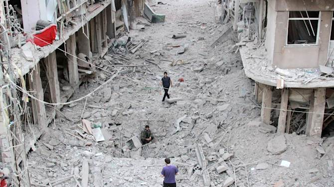 People walk on the rubble of damaged buildings after a Syrian military helicopter allegedly droped barrel bombs over the city of Daraya, southwest of the capital Damascus, September 29, 2014