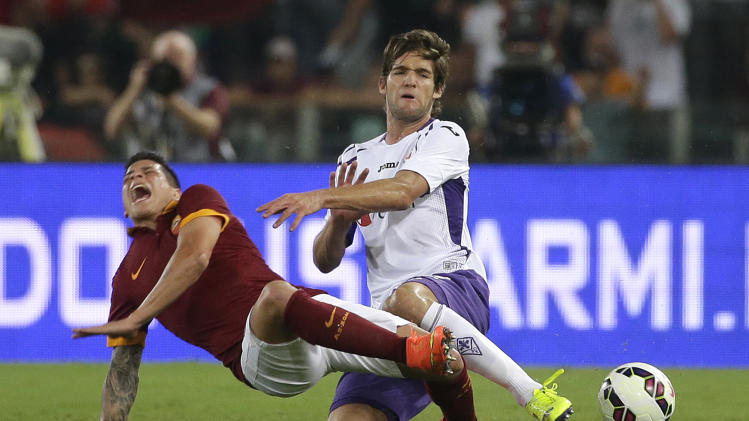 Roma forward Juan Manuel Arevalos Iturbe, left, is fouled by Fiorentina defender Manuel Pasqual during a Serie A soccer match between Roma and Fiorentina at Rome's Olympic stadium, Saturday, Aug 30, 2014. (AP Photo/Alessandra Tarantino)