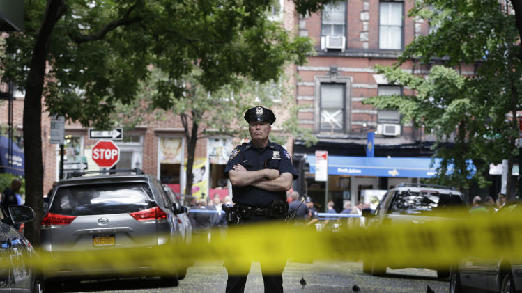A police officer stands near a crime scene on Monday, July 28, 2014 in New York. Authorities say a sex-assault suspect got in a shootout with law enforcement in New York City that wounded the suspect, two federal marshals and a police officer. (AP Photo/Seth Wenig)