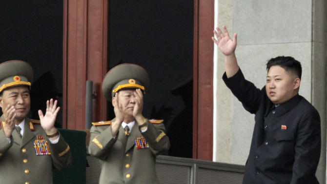 FILE - In this April 14, 2012 file photo, North Korean leader Kim Jong Un, right, waves as North Korean military officers clap during a mass meeting of North Korea's ruling party at a stadium in Pyongyang, North Korea. North Korean state media made the announcement Wednesday, July 18, 2012 in a special bulletin that Kim has been promoted to marshal, the military's highest rank. (AP Photo/Ng Han Guan, File)