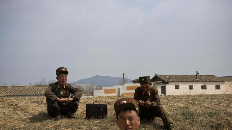 North Korean soldiers sit on the side of a road  in south of Kaesong, North Korea near the demilitarized zone which separates the two Koreas on Wednesday, April 24, 2013. For weeks, North Korea has threatened to attack the U.S. and South Korea for holding joint military drills and for supporting U.N. sanctions. Washington and Seoul said they've seen no evidence that Pyongyang is actually preparing for a major conflict, though South Korean defense officials said the North appears prepared to test-fire a medium-range missile. (AP Photo/David Guttenfelder)