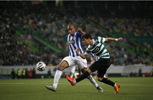 Sporting's Andre Martins shoots near Porto's Fernando Reges during their Portuguese premier league soccer match at Alvalade stadium in Lisbon