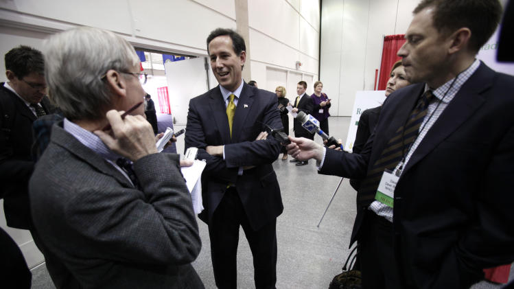 Former Penn. Sen. Rick Santorum, center, talks with reporters before speaking at the Iowa Renewable Fuels Summit, Tuesday, Jan. 25, 2011, in Des Moines, Iowa. (AP Photo/Charlie Neibergall)