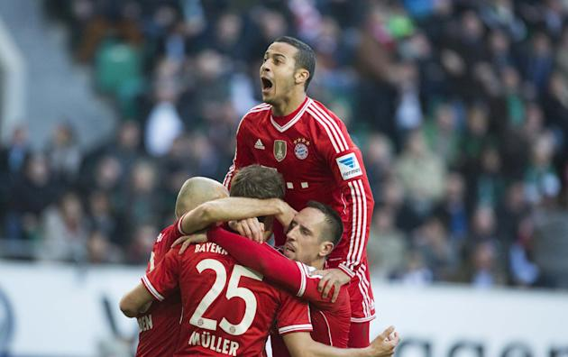 Bayern's Thiago Alcantara of Spain, top, Bayern's Arjen Robben of the Netherlands, Bayern's Thomas Mueller, and Bayern's Franck Ribery of France, bottom from left, celebrate after Muel