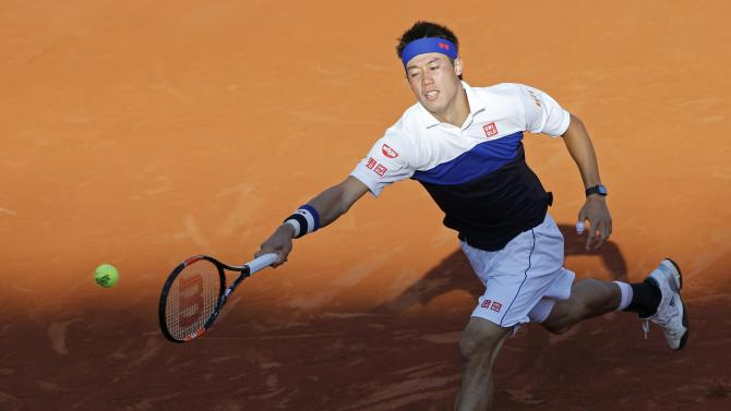 Kei Nishikori of Japan returns the ball to Jo-Wilfried Tsonga of France during their men's quarter-final match during the French Open tennis tournament at the Roland Garros stadium in Paris