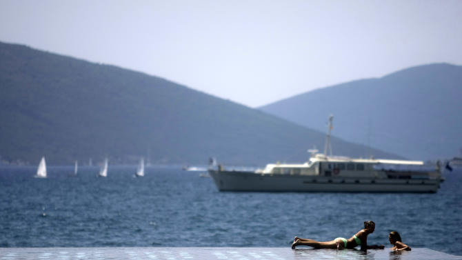In this photo taken Sunday, Aug. 12, 2012, two women sunbathe at the Porto Montenegro resort next to the town of Tivat in Montenegro. The newly developed resort of Porto Montenegro features a huge black and white tiled infinity pool with a panoramic view of the turquoise color Adriatic sea, Venetian style waterfront luxury homes, a vibrant nautical village with top brand shops and restaurants, and a vast superyacht marina for some of the finest boats afloat.(AP Photo/ Marko Drobnjakovic)