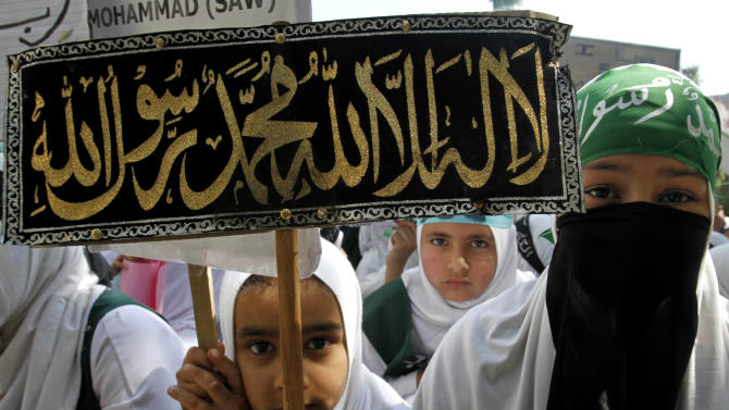 "Kashmiri Muslim students hold placards as they participate in a protest rally against an anti-Islam film called ""Innocence of Muslims"" that ridicules Islam's Prophet Muhammad, in Srinagar, India, Saturday, Sept. 22, 2012. The placard reads: ""There is no God but Allah and Muhammad is his messenger."" (AP Photo/Mukhtar Khan)"
