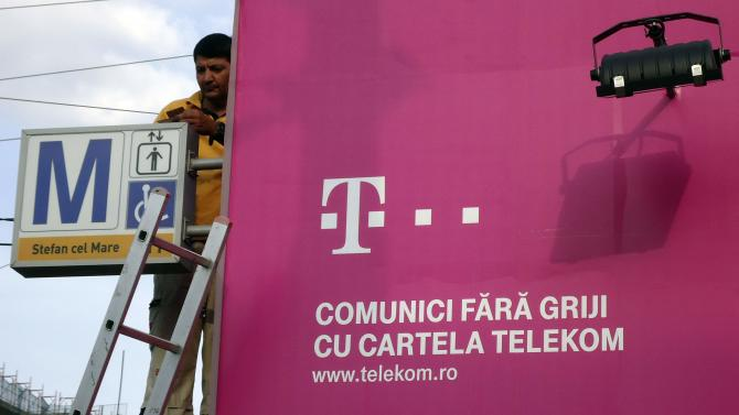 A worker fixes an advertising of Telekom on a metro entrance in Bucharest