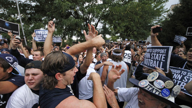 Penn State University linebacker Michael Mauti, second from left foreground, and his teammates are greeted by a pep rally of supporters on the way to a morning workout outside the Lasch Football building on the Penn State main campus in State College, Pa., Tuesday, July 31, 2012. (AP Photo/Gene J. Puskar)