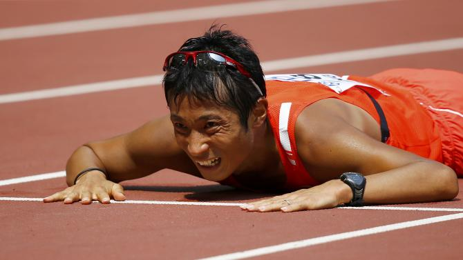 Takayuki Tanii of Japan lies on the floor after finishing third in the men's 50 km race walk final during the 15th IAAF World Championships at the National Stadium in Beijing
