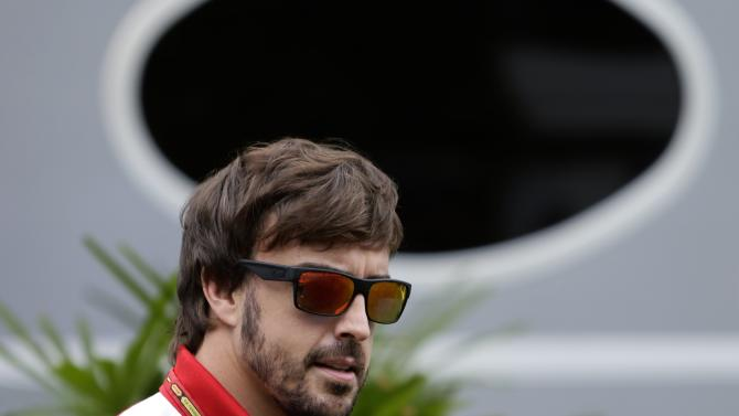 Ferrari Formula One driver Fernando Alonso of Spain arrives at the paddock ahead of the third practice session of the Singapore F1 Grand Prix in Singapore