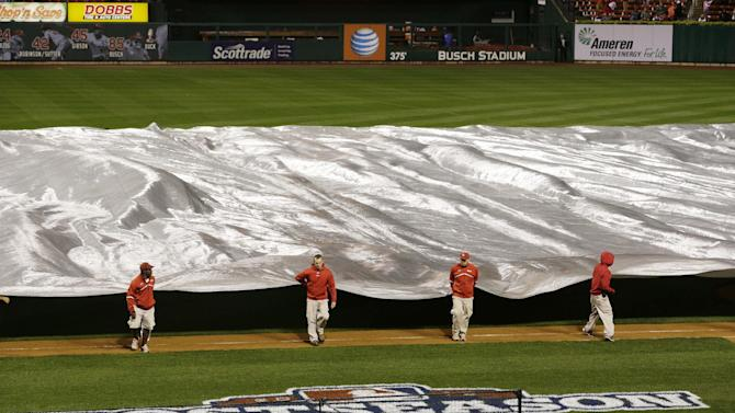 Ground crew takes tarp of of the field to prepare during the rain delay of Game 3 of baseball's National League championship series between the St. Louis Cardinals and the San Francisco Giants Wednesday, Oct. 17, 2012, in St. Louis. (AP Photo/Patrick Semansky)