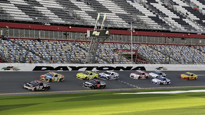 Denny Hamlin (11) and Kyle Busch (18) lead a group of cars through the front stretch during practice for the NASCAR Sprint Unlimited Shootout auto race at Daytona International Speedway, Friday, Feb. 15, 2013, in Daytona Beach, Fla. (AP Photo/John Raoux)