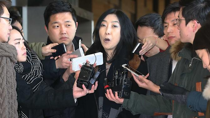 In this Wednesday, Jan. 7, 2015, photo, California-resident Shin Eun-mi, center, talks to the reporters at Seoul District Prosecutors' Office in Seoul, South Korea. South Korean officials said Friday, Jan. 9 they were considering whether to deport the Korean-American woman accused of praising rival North Korea during a recent lecture. (AP Photo/Yonhap, Park Ji-ho)  KOREA OUT