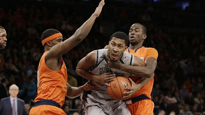 Georgetown's Mikael Hopkins, center, is defended by Syracuse's Baye Keita, right, and Syracuse's C.J. Fair, left, during the first half of an NCAA college basketball game at the Big East Conference tournament Friday, March 15, 2013, in New York